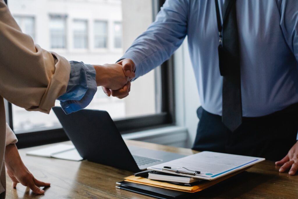 Business persons shaking hands over desk