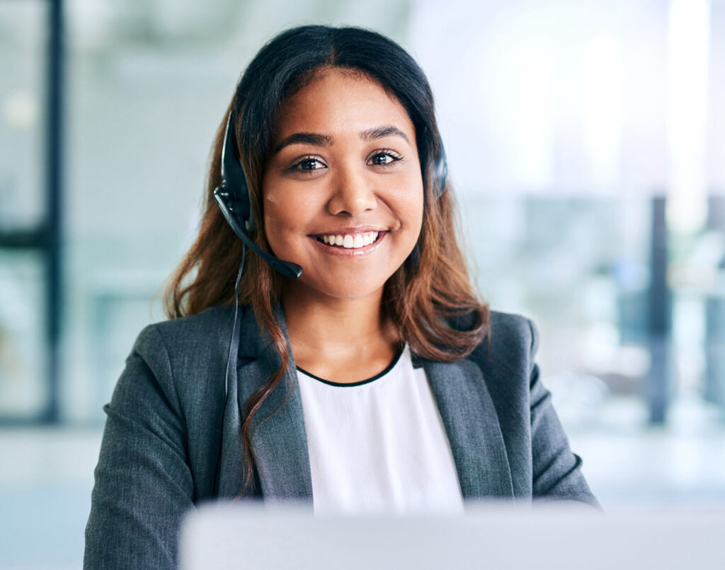 Shot of a young woman using a headset and laptop in a modern office