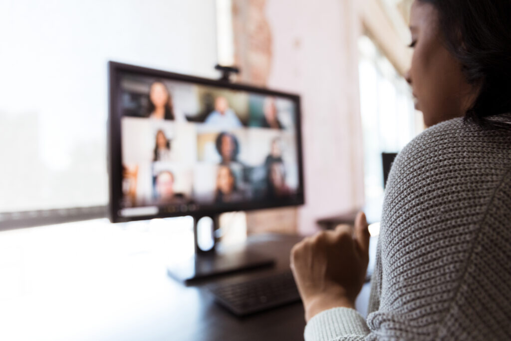 The mid adult woman video conferences with co-workers from her home office during the coronavirus shutdown.