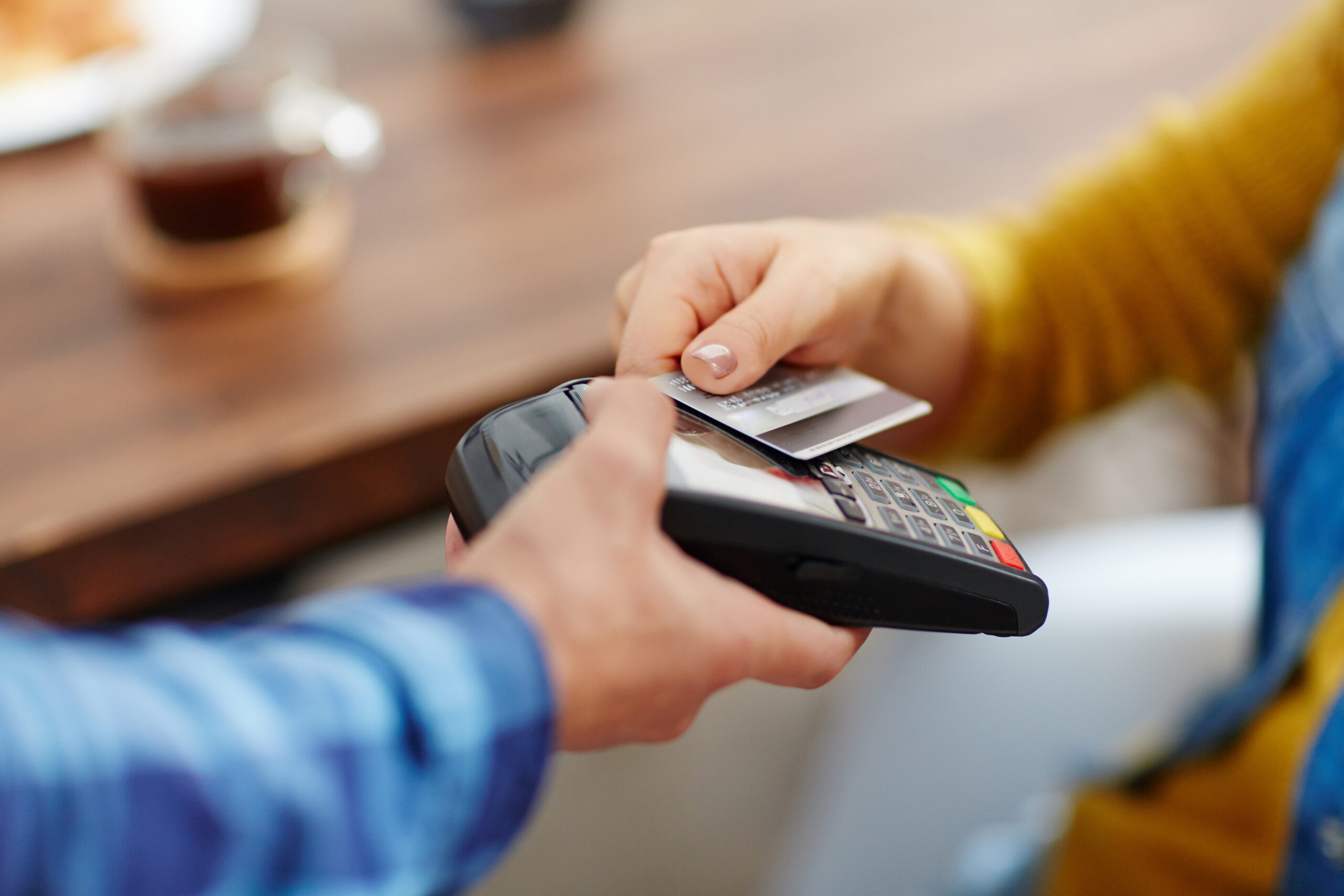 Close-up of unrecognizable customer choosing contactless payment using credit card while waitress accepting payment over nfc technology