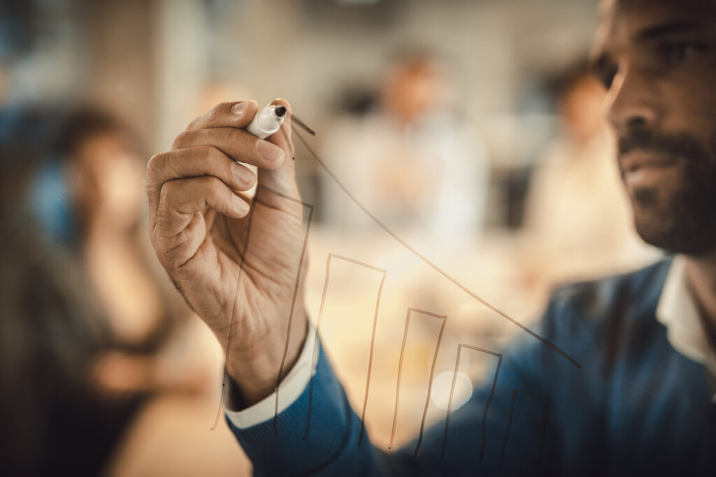 Close up of a businessman drawing diagram of progress on a glass wall.
